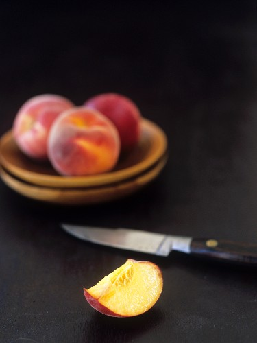 Peach wedge and whole peaches with knife