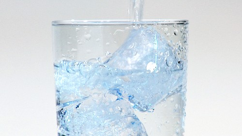 Pouring water into a glass of ice cubes (close-up)