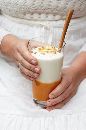 A woman holding a glass of apricot dessert