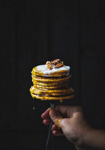 A hand holding a fork stuck into a stack of pumpkin pancakes