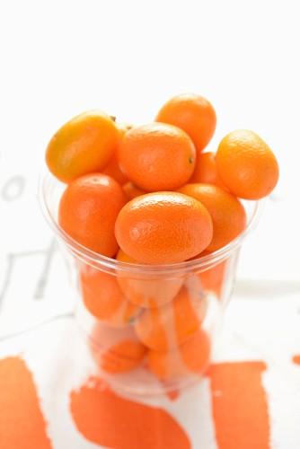 Several kumquats in a glass