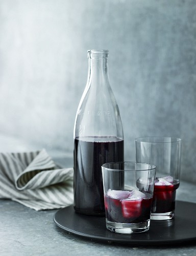 Elderberry juice in glasses and a bottle