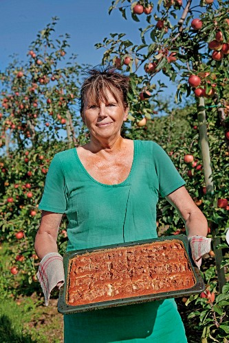 A woman holding an apple cake tray bake