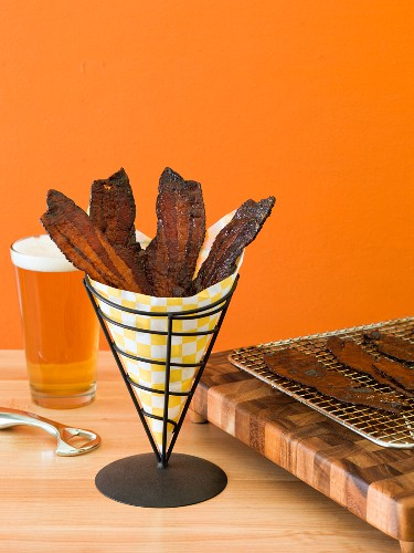 Candied bacon strips in a paper cone with more on a wire rack