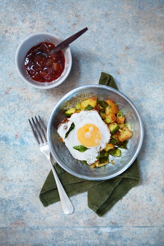 Fried potatoes with courgettes and a fried egg (seen from above)