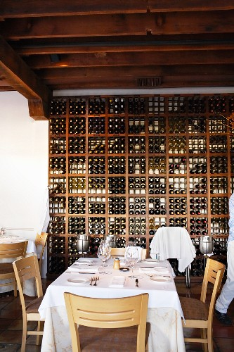 Weiss gedeckter Restauranttisch vor hohem Weinregal unter dunkler Balkendecke