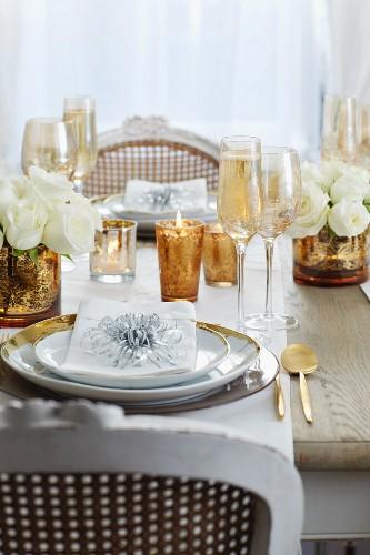 Festlich gedeckter Tisch mit vergoldeten Vasen, Goldrandteller und Goldbesteck