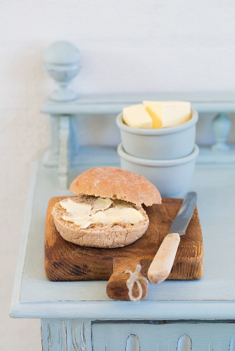 A buttered roll with a knife on a rustic wooden board