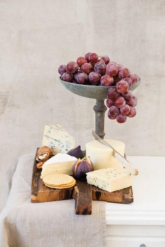 Käseplatte mit Havarti, Brie, dänischem Kümmelkäse, Blauschimmelkäse, Feigen, Kräckern, Trauben und Nüssen
