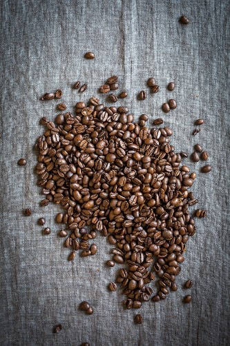 Coffee beans on a grey linen cloth