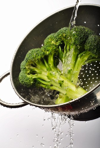 Broccoli Being Washed in a Colander