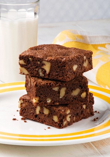 Three Walnut Brownies Stacked on a Plate; Glass of Milk