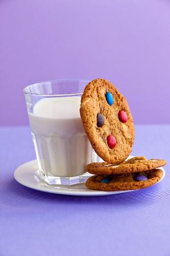 Cookies mit Schokolinsen und ein Glas Milch