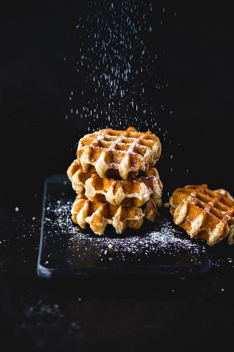 Belgian waffles being dusted in icing sugar