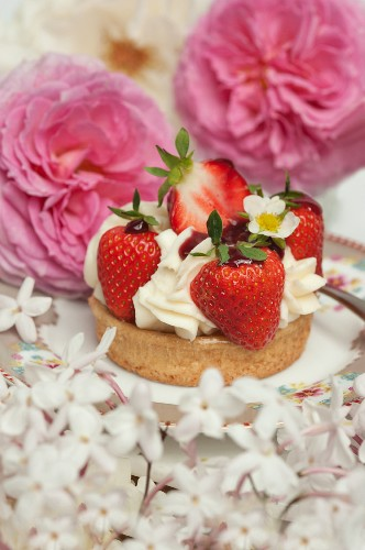 Strawberry cake with cream surrounded by summery roses and jasmine blossoms