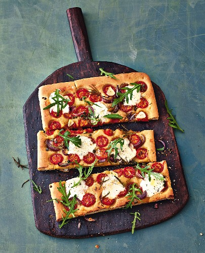 Focaccia with cherry tomatoes and taleggio on a wooden board