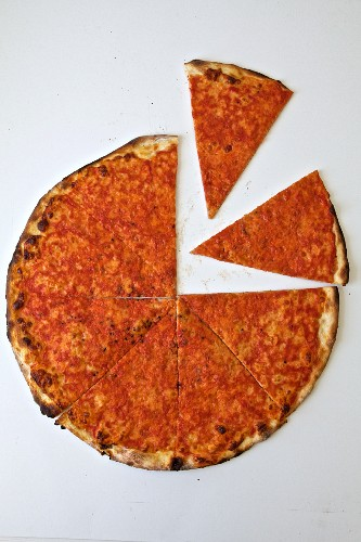 A sliced thin-crust pizza on a white background (seen from above)