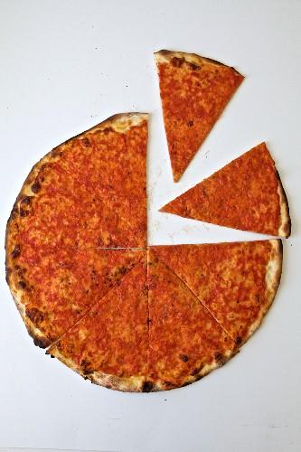 Dünne Pizza, angeschnitten auf weissem Untergrund (Aufsicht)