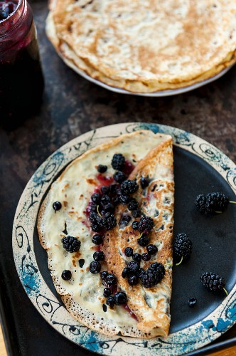 Crepes with black currant jam decorated with blackberries and bluberries