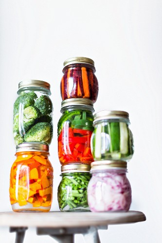 Preserving jars of freshly pickled vegetables stacked on an old stool