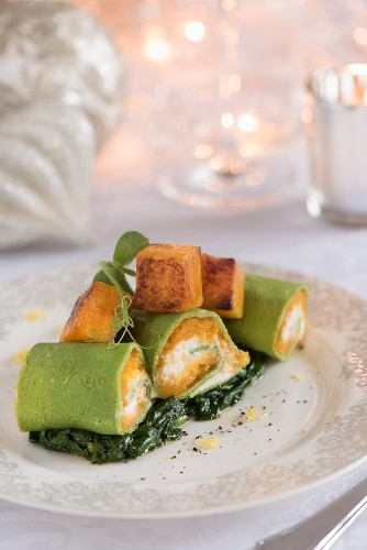 A stuffed pumpkin pasta roll on a bed of cooked spinach for Christmas