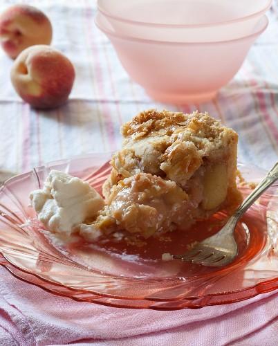 Teilweise gegessenes Stück Pfirsichpie mit Schlagsahne