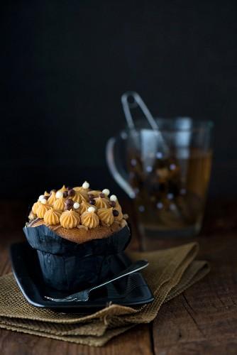 Salted-Caramel-Cupcake vor einer Tasse Kräutertee