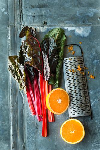 Mangold , halbierte Orange und Küchenreibe