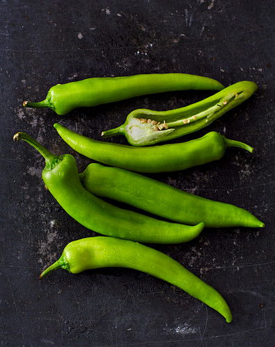 Green chilli peppers on a wooden surface