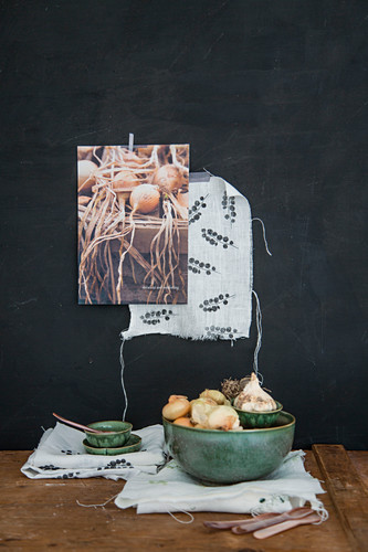 Green bowl of onions and garlic on printed cloth