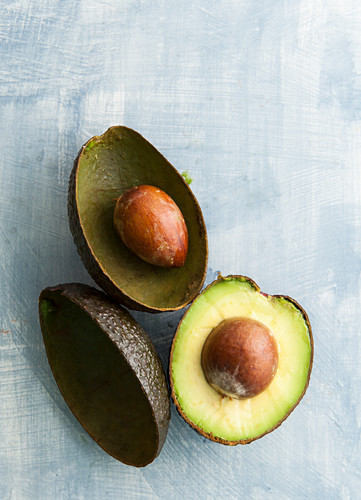 Avocado halves and empty shells with stones