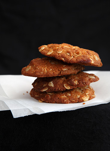 A stack of oatmeal cookies on paper in front of black background