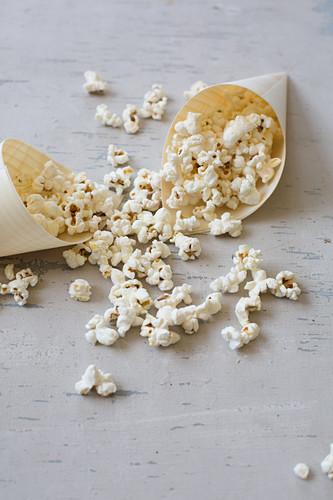 Popcorn in Papiertüte und auf hellem Untergrund