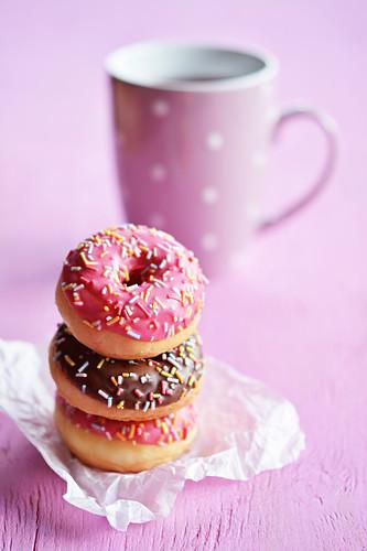 Drei gestapelte Mini-Donuts mit Glasur und Zuckerstreuseln vor Teetasse