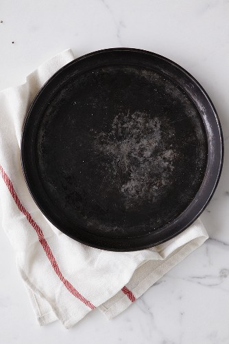 Round baking tray on tea towel (overhead view)