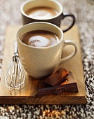 Two mugs of hot chocolate on a wooden board