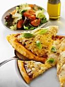 Stück Pizza mit Käse auf Heber, Salatteller im Hintergrund