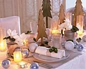 Weihnachtstisch mit Alpenveilchen und Holztannenbäumen