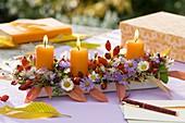 Herbstgesteck mit Blumen, Hagebutten und Kerzen auf Tisch