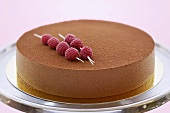 Chocolate mousse cake with skewered raspberries
