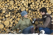 Young couple sitting by stack of wood with Thermos flask