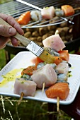 Brushing fish kebabs with herb oil