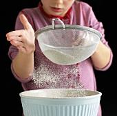 Girl sieving flour