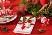 Serviette mit Ilexzweig und Nussstern auf Weihnachtstisch
