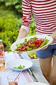 Mädchen hält Teller mit Tomaten-Rucola-Salat