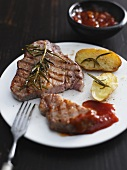 A grilled steak with potatoes, barbeque sauce and rosemary