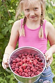 A blonde girl holding a bucket of raspberries