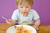Small boy with spaghetti in his mouth