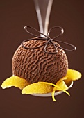 Chocolate ice cream with orange segments on a spoon