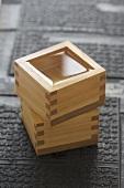 Two square sake bowls, one containing sake